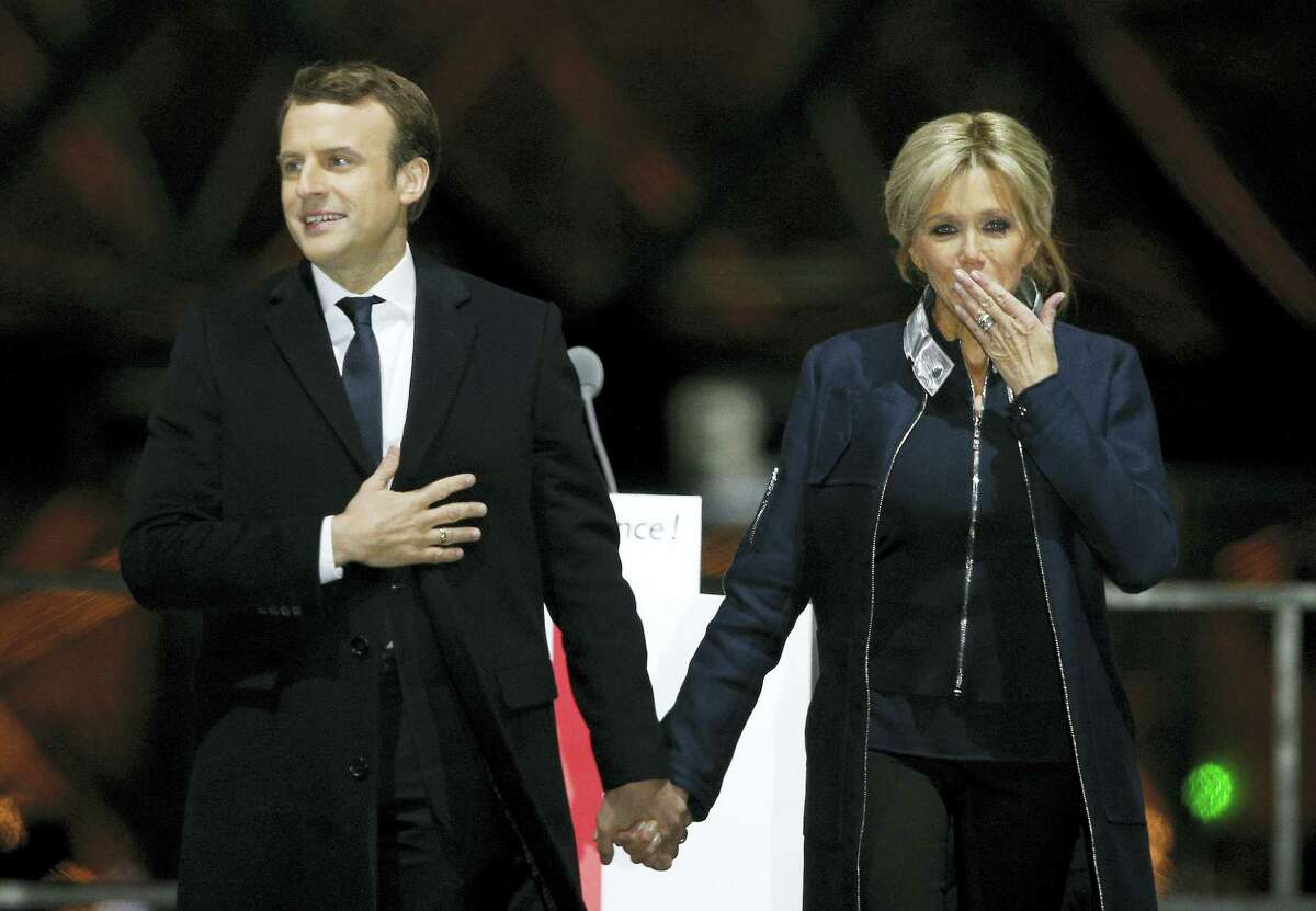 """French President-elect Emmanuel Macron holds hands with his wife Brigitte during a victory celebration outside the Louvre museum in Paris, France. Speaking to thousands of supporters from the Louvre Museum's courtyard, Macron said that France is facing an """"immense task"""" to rebuild European unity, fix the economy and ensure security against extremist threats."""