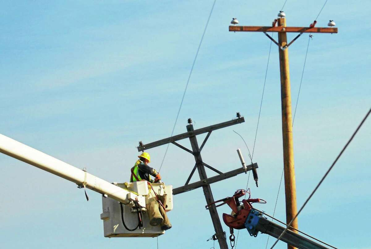 A worker moves utility wires from a damaged poles in this file photo.