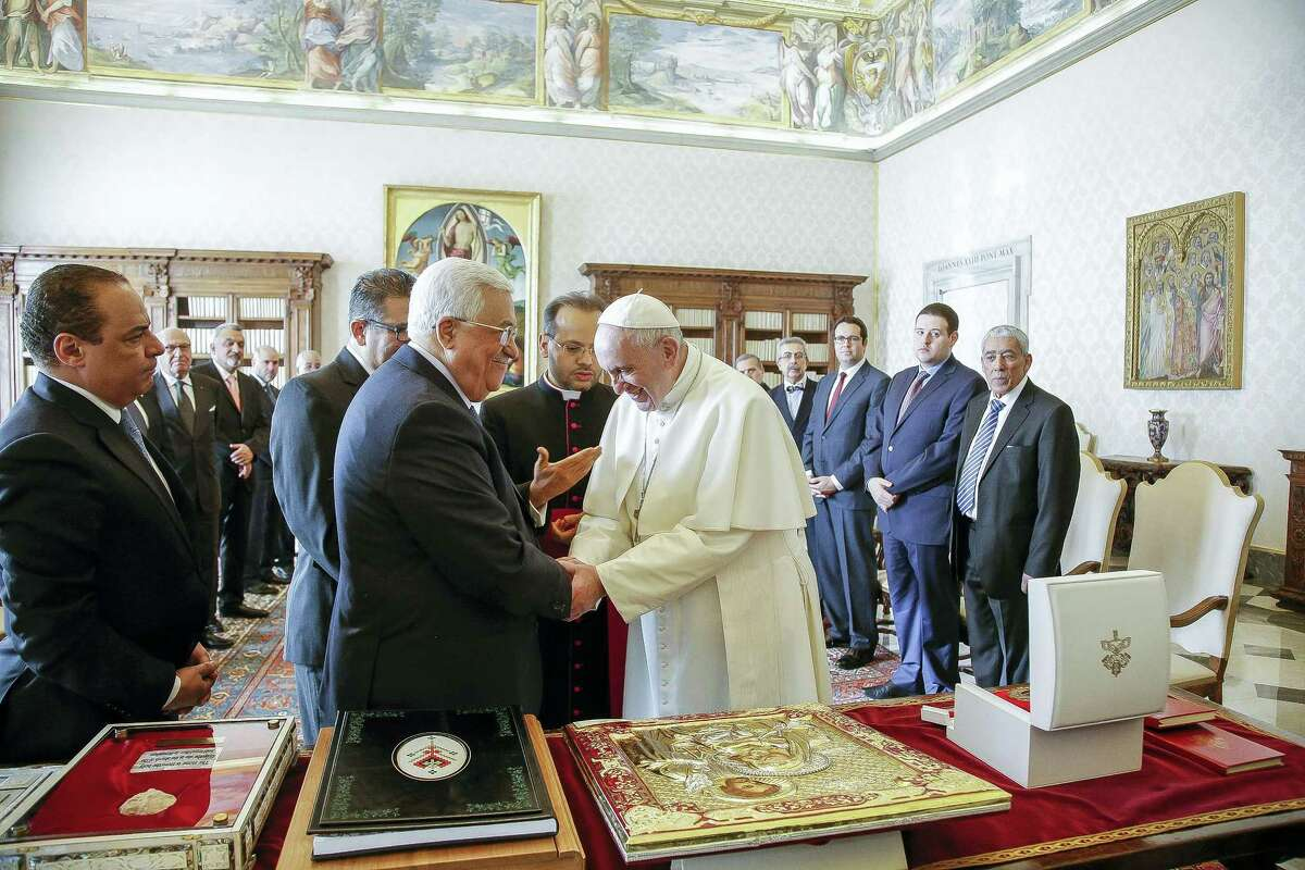 Pope Francis shakes hands with Palestinian President Mahmoud Abbas during a private audience at the Vatican.