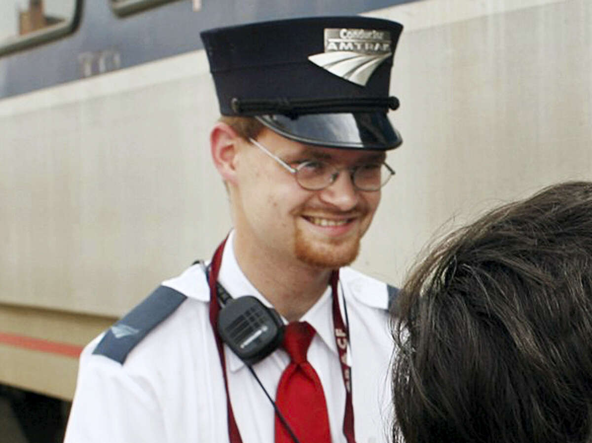This Aug. 21, 2007, file photo shows Amtrak assistant conductor Brandon Bostian outside a train at the Amtrak station in St. Louis. Philadelphia prosecutors said Tuesday, May 9, 2017, Bostian, the speeding Amtrak engineer involved in the May 12, 2015, derailment that killed eight people and injured about 200 others, won't be charged.