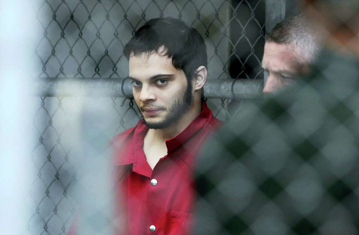 Esteban Santiago is taken from the Broward County main jail as he is transported to the federal courthouse in Fort Lauderdale, Fla. Amy Beth Bennett — South Florida Sun-Sentinel via AP