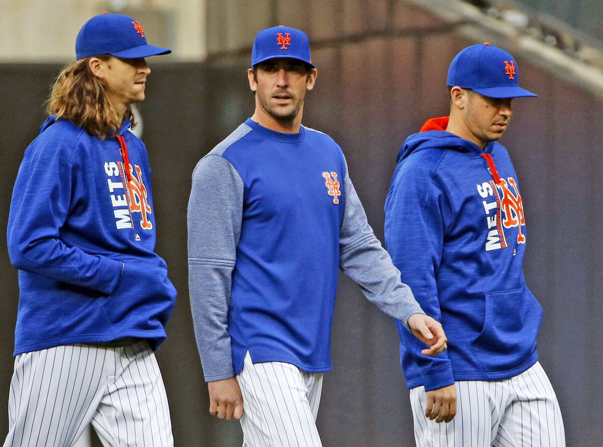 New York Mets starting pitchers Noah Syndergaard, left, and Matt Harvey, center, walk to the dugout before the team's baseball game against the San Francisco Giants, Tuesday. before the game, Harvey publicly apologized for skipping out on a game last wekeend.