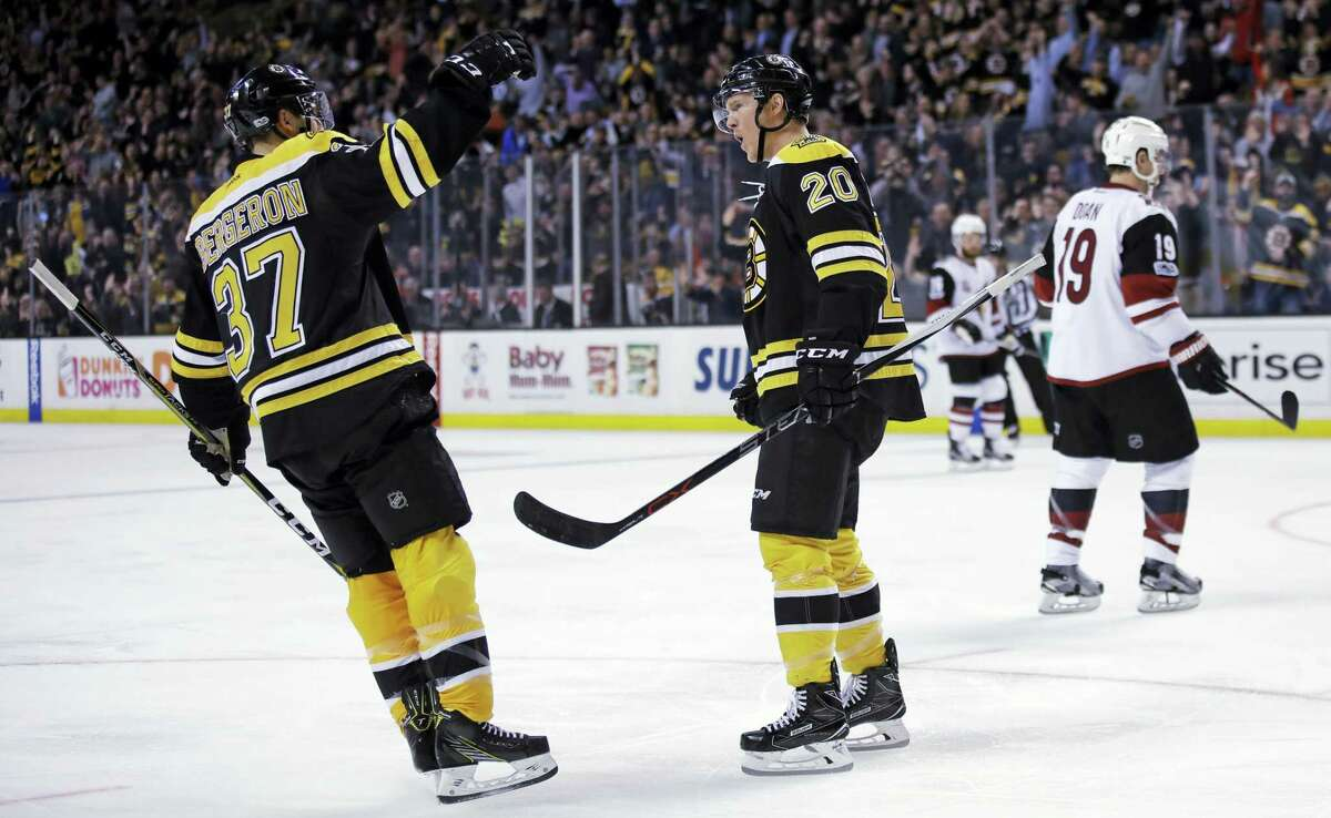 Boston Bruins center Riley Nash (20) celebrates after his short-handed goal off Arizona Coyotes goalie Mike Smith during the second period of an NHL hockey game in Boston, Tuesday, Feb. 28, 2017. At left is Bruins center Patrice Bergeron. (AP Photo/Charles Krupa)