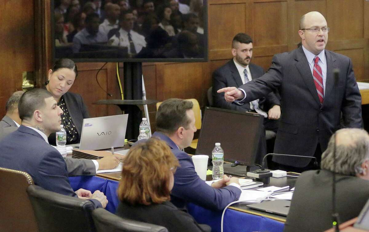 Assistant district attorney Patrick Haggan points at former New England Patriots tight end Aaron Hernandez as Haggan delivers his opening statement to the jury during the first day of Hernandez's double murder trial at Suffolk Superior Court Wednesday in Boston.