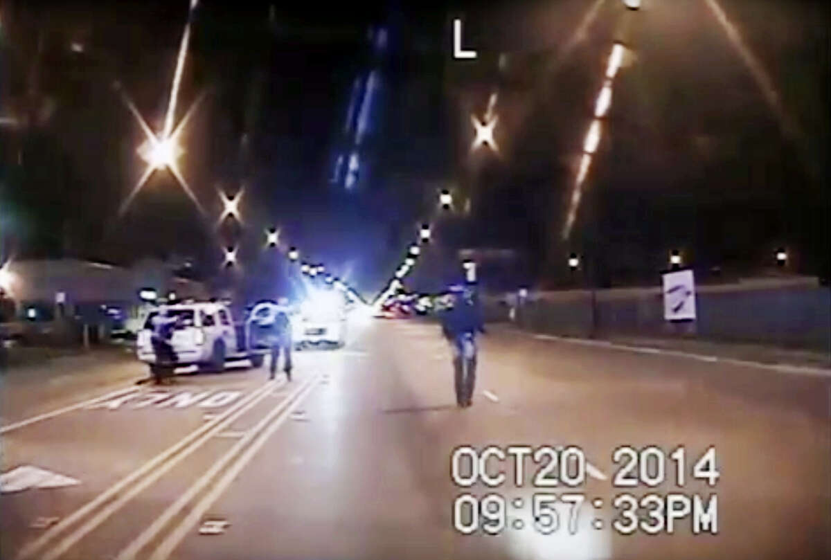 In this Oct. 20, 2014, frame from dash-cam video provided by the Chicago Police Department, Laquan McDonald, right, walks down the street moments before being fatally shot by CPD officer Jason Van Dyke sixteen times in Chicago. The Department of Justice is poised to release its report detailing the extent of civil rights violations committed by the Chicago Police Department. The next stage after the Friday, Jan. 13, 2017, release will be negotiations between the DOJ and the city.