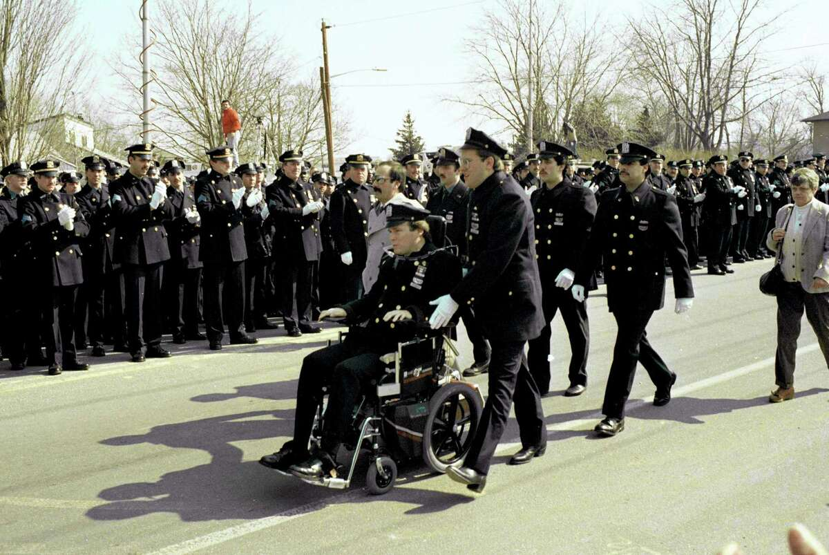 In 1988, paralyzed police officer Steven McDonald receives applause from members of the New York City Police Department as he arrives for funeral services at Seaford, N.Y., for slain officer Edward Byrne. McDonald, who was paralyzed by a bullet and became an international voice for peace after he publicly forgave the gunman, died Tuesday, Jan 10, 2017 at the age of 59.
