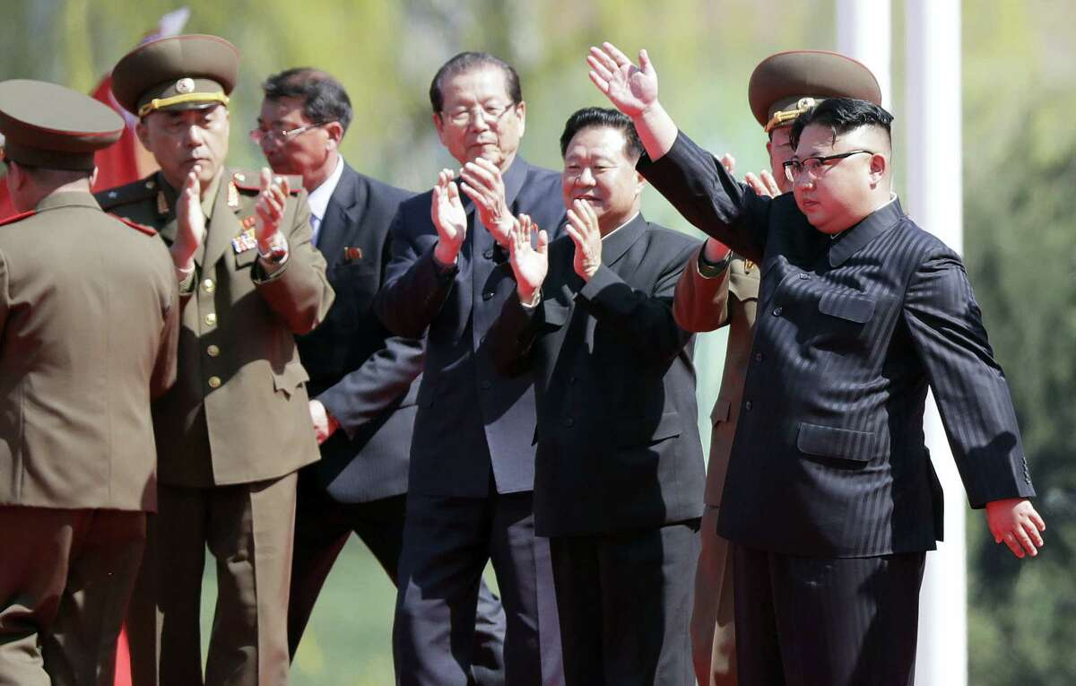 In this April 13, 2017 photo, North Korean leader Kim Jong Un, right, waves during the opening ceremony of the Ryomyong residential area, a collection of more than a dozen apartment buildings in Pyongyang, North Korea.
