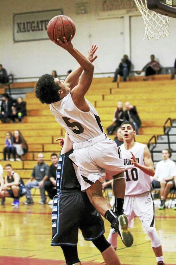 In a game with a near-chaotic pace, Dontae Thomas gets in for a layup while Joel Villanueva sets for the rebound Wednesday against Oxford at Torrington High School. Photo: Photo By Marianne Killackey  / 2015