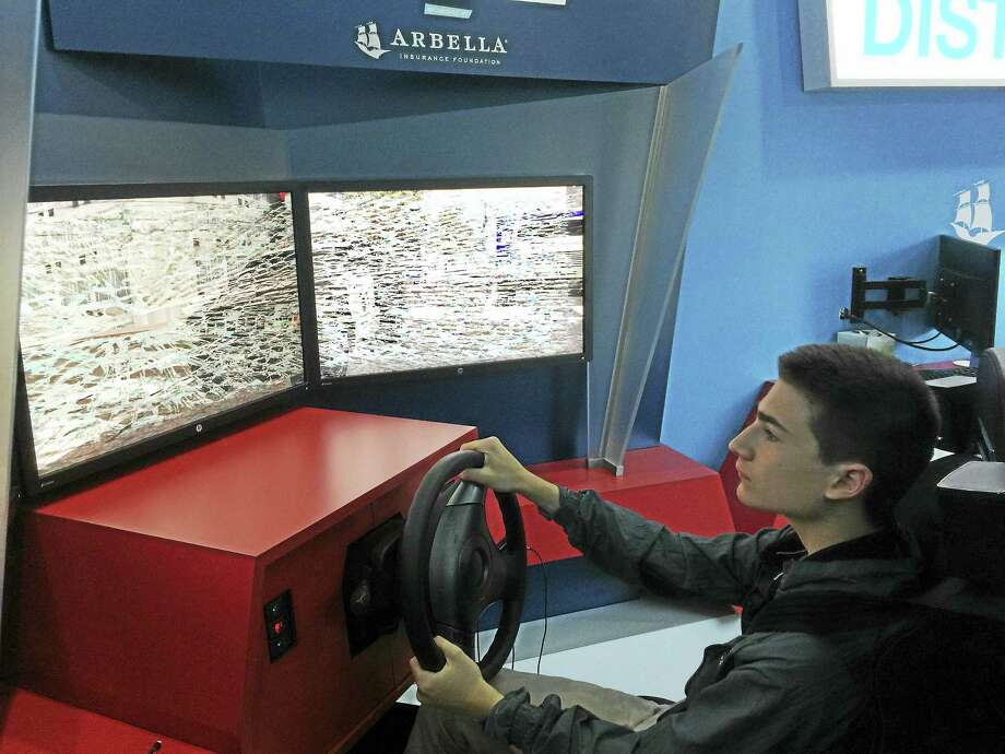 """Adam Choquette pilots his way through the """"Distractology"""" simulator at Northwestern Regional High School 7 Monday. The simulator impresses upon its drivers the consequences of distracted driving — texting, using Snapchat and other diversions while they're behind the wheel. Photo: Ben Lambert — The Register Citizen"""