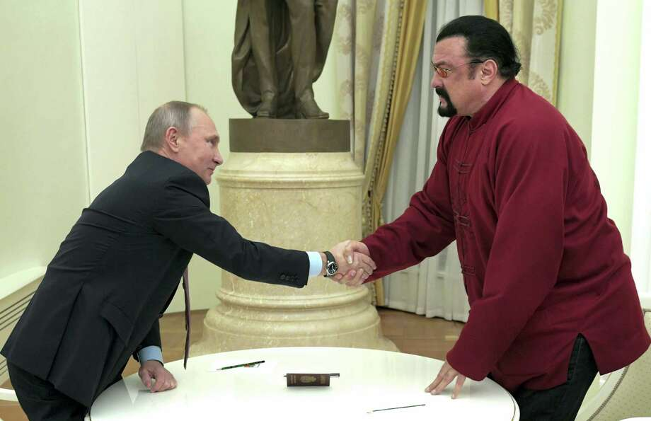 "FILE - In this file photo dated Nov. 25, 2016, Russian President Vladimir Putin shakes hands with U.S. actor Steven Seagal in the Kremlin in Moscow, during a ceremony to award a Russian passport, seen on table, to Seagal.  A statement issued by the Ukrainian Security Service Friday May 5, 2017, said Seagal has been banned from entering the country for five years ""on the basis of Ukrainian national security"" without elaborating on the reason for the ban. Photo: Alexei Druzhinin/Sputnik — Kremlin Pool Photo Via AP, FILE / POOL SPUTNIK KREMLIN"