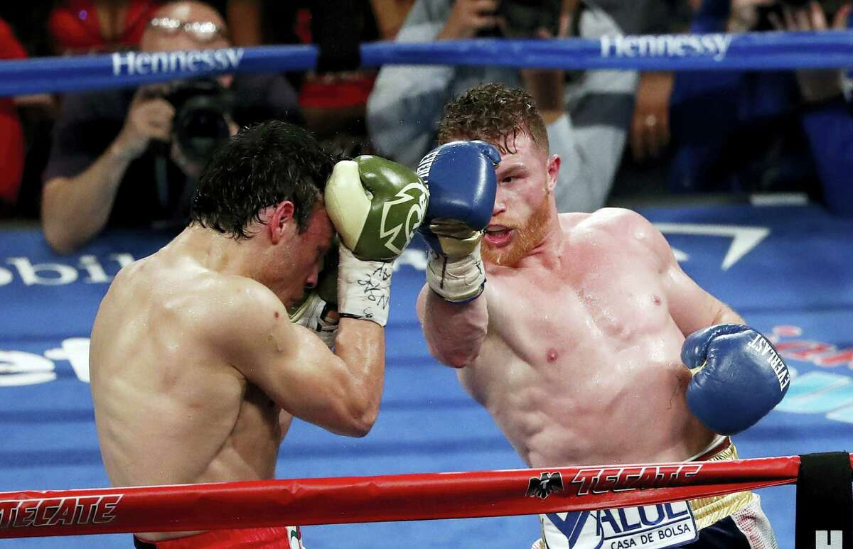Canelo Alvarez, of Mexico, right, punches Julio Cesar Chavez Jr., of Mexico, during their catch weight boxing match Saturday, May 6, 2017 in Las Vegas.