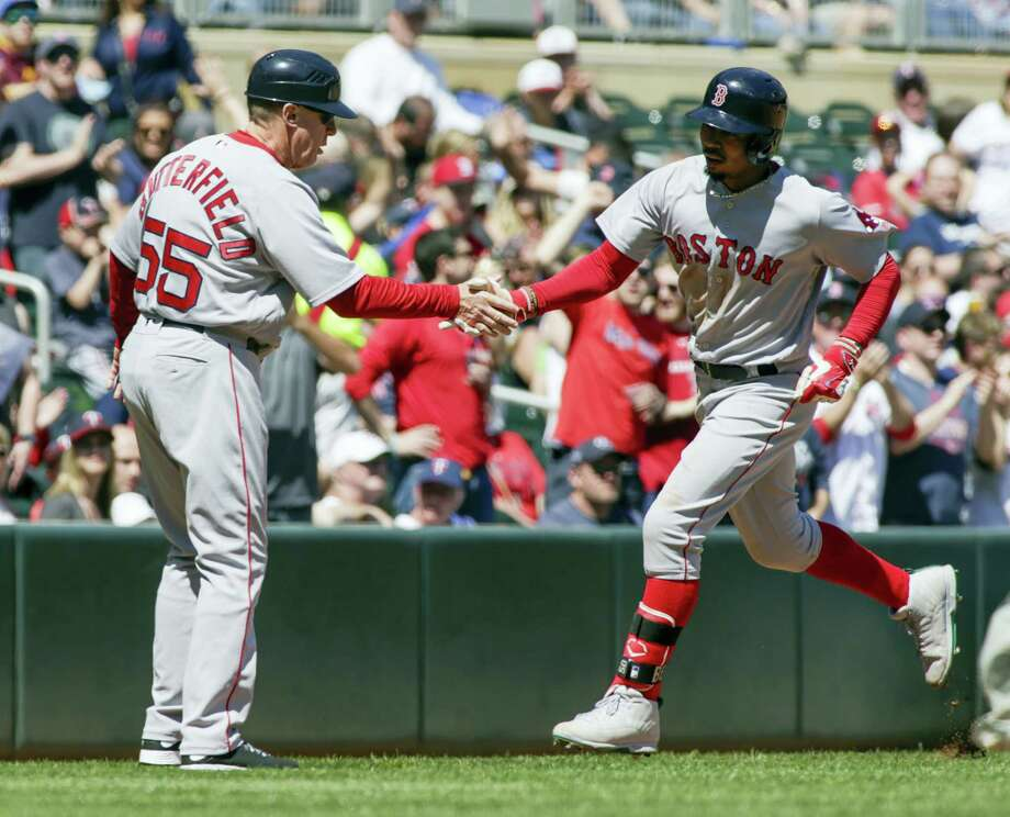 Mookie Betts, right, is congratulated by third base coach Brian Butterfield after hitting a solo home run in the fifth inning Sunday. Photo: Paul Battaglia — The Associated Press  / FR1768 AP