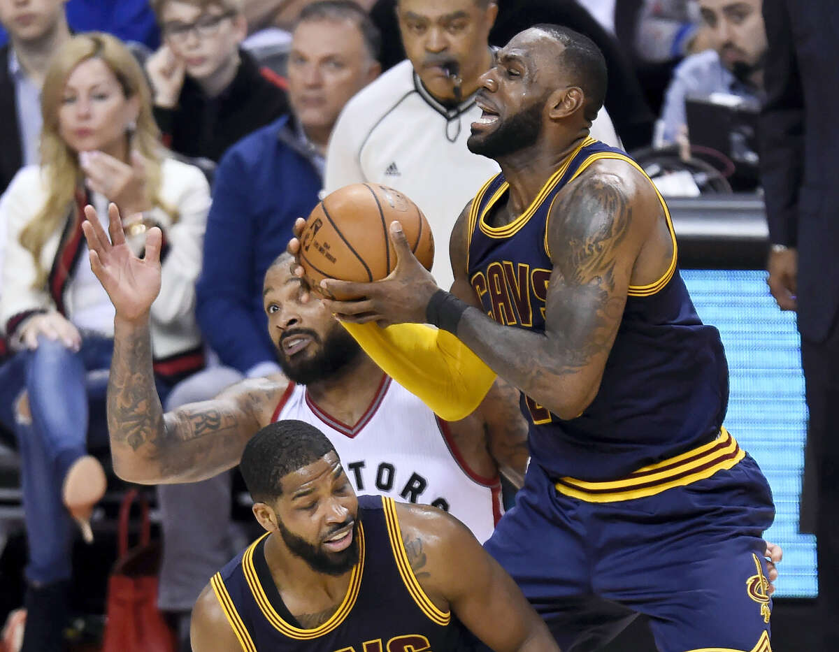 The Cavaliers' forward LeBron James (23) and the Raptors' P.J. Tucker battle for the ball by Cavaliers center Tristan Thompson during second half Sunday.
