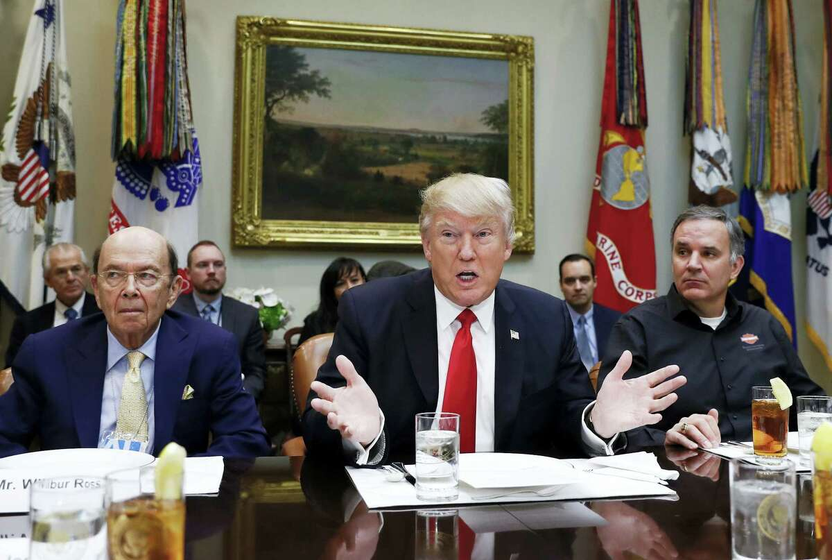 In this Feb. 2, 2017 photo, President Donald Trump, flanked by then-Commerce Secretary-designate Wilbur Ross, left, and Harley Davidson President and CEO Matt Levatich, talks to media before a lunch meeting with Harley Davidson executives and union representatives in the Roosevelt Room of the White House in Washington.