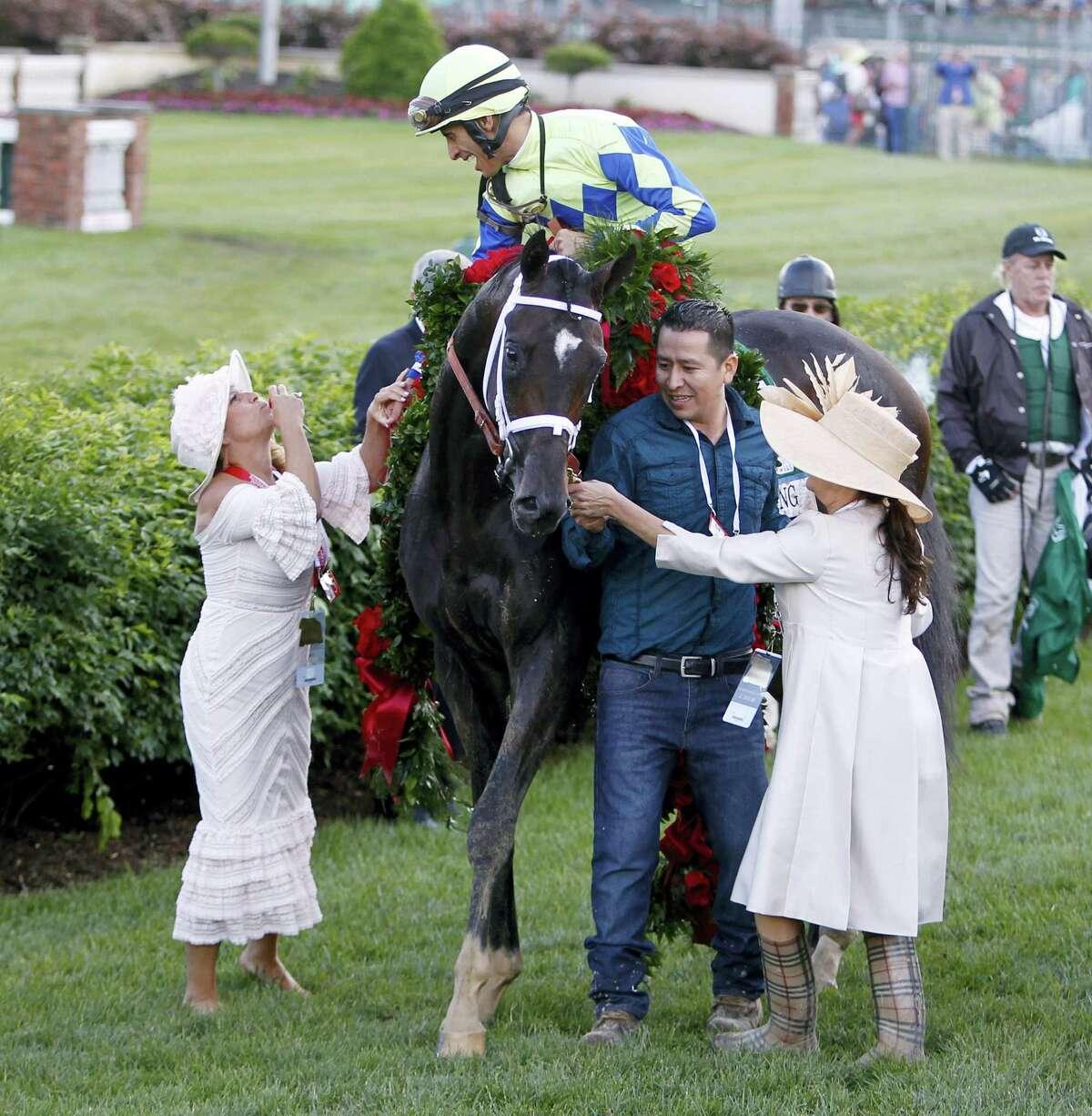John Velazquez celebrates with Always Dreaming owners Mary Ellen Bonomo and Teresa Viola.