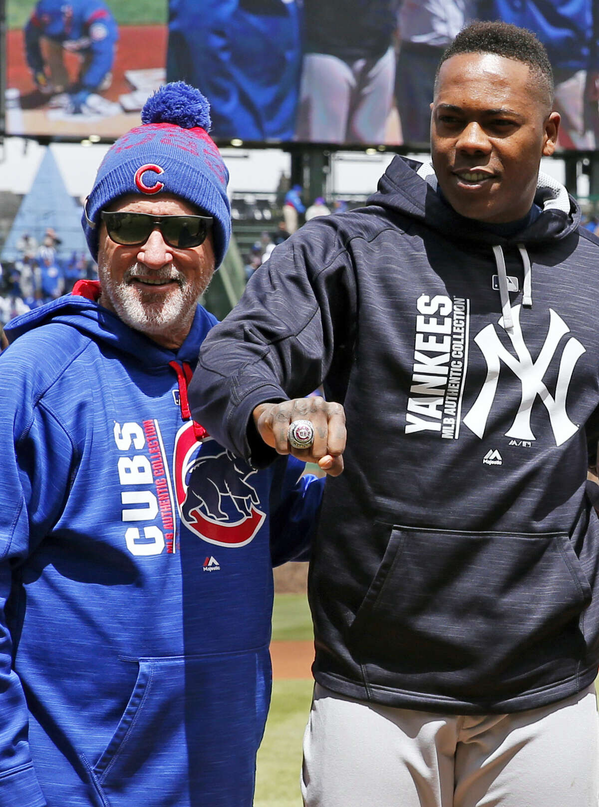 Yankees relief pitcher Aroldis Chapman, right, stands with Cubs manager Joe Maddon as Chapman received his 2016 World Series ring on Friday.
