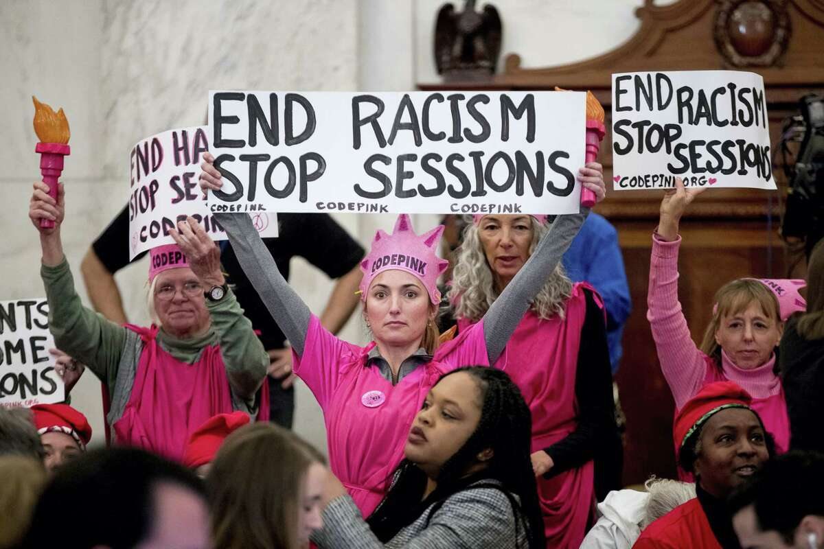CodePink activists, including co-founder Medea Benjamin, right, hold up signs against Attorney General-designate, Sen. Jeff Sessions, R-Ala., on Capitol Hill in Washington on Jan. 10, 2017 as he testifies at his confirmation hearing before the Senate Judiciary Committee.
