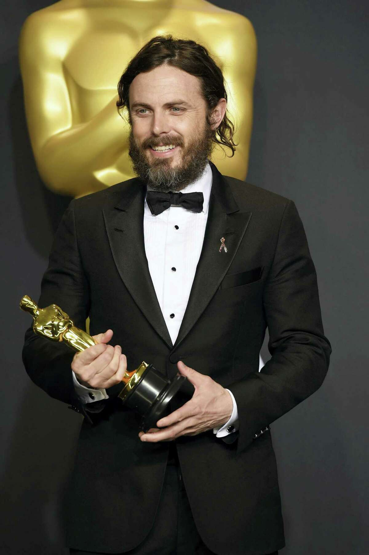 """Casey Affleck poses in the press room with the award for best actor in a leading role for """"Manchester by the Sea"""" at the Oscars on Feb. 26, 2017 at the Dolby Theatre in Los Angeles."""