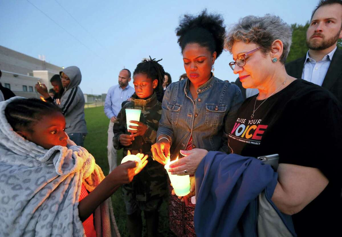 Hope Waters, left, her brother Jeremiah, center rear, and their mother Yulise, center right, light candles with Linda Abrasion Evans, right, during a candle light vigil for Jordan Edwards in Balch Springs, Texas, Thursday.