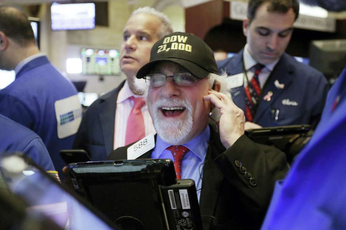 """Trader Peter Tuchman wears a """"Dow 21,000"""" hat as he works on the floor of the New York Stock Exchange Wednesday."""
