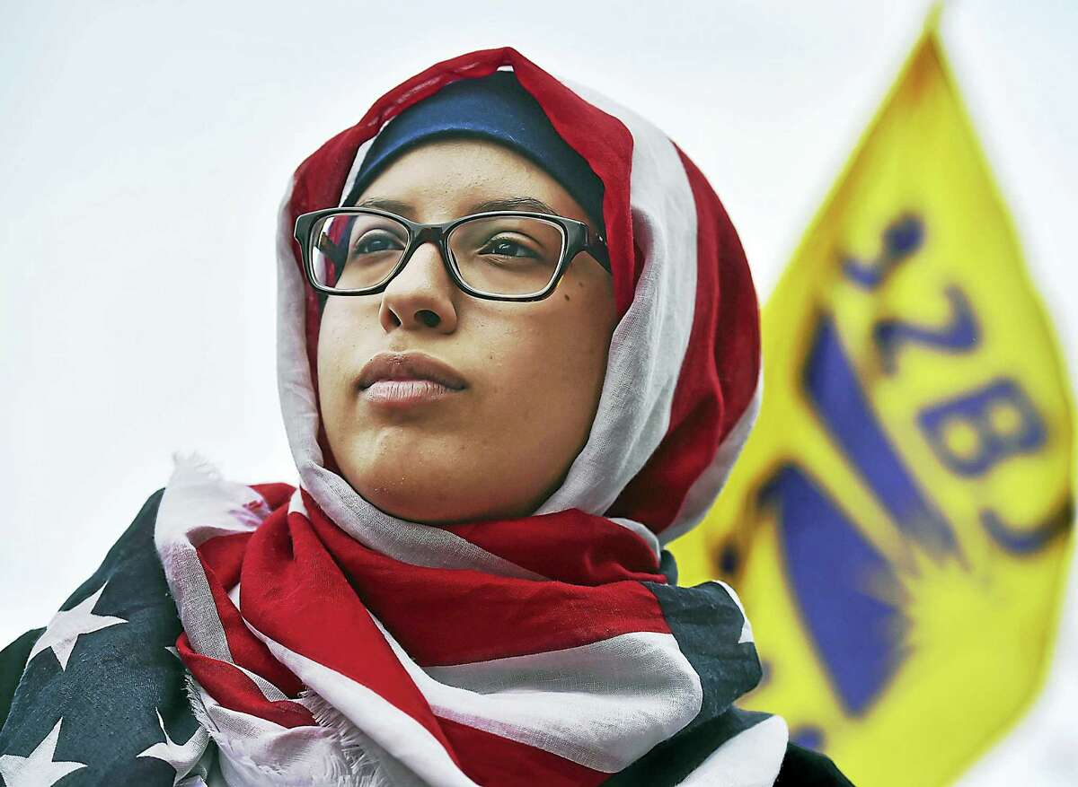"""Catherine Avalone — New Haven Register Elaf Al-Wohaibi wearing an American Flag hajib, a scarf she purchased from Old Navy, joins hundreds of residents from across Connecticut at the """"Here to Stay"""" immigrant rights rally, Saturday, at the State Capitol in Hartford. Al-Wohaibi said, """"I have received compliments from veterans when I am wearing my hajib."""""""
