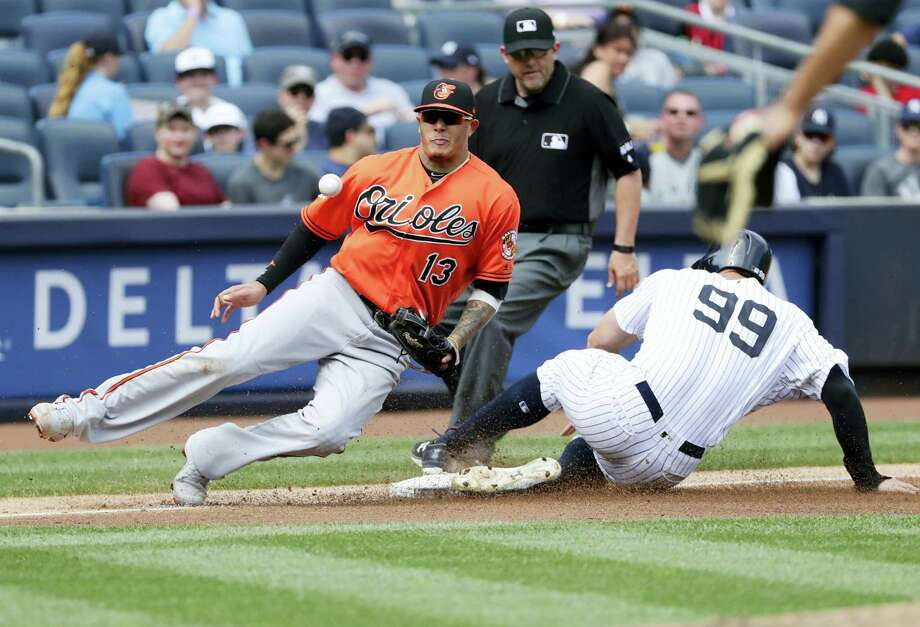 New York's Aaron Judge steals third base as Baltimore's Manny Machado fields the throw during the fourth inning of the Orioles' 7-4 win in 11 innings to avoid the three-game sweep. Photo: FRANK FRANKLIN II - THE ASSOCIATED PRESS  / Copyright 2017 The Associated Press. All rights reserved.