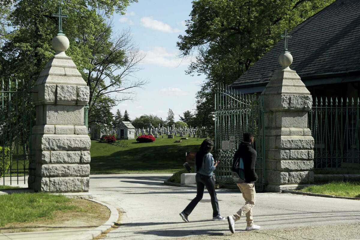 People walk past a gate to Holy Cross Cemetery, Wednesday, May 3, 2017, in Yeadon, Pa. The body of 19th century serial killer Dr. H. H. Holmes is being exhumed from the cemetery in suburban Philadelphia at the request of his great-grandchildren, who hope identifying his remains will quell centuries-old rumors that he conned his way out of his execution and escaped from prison.