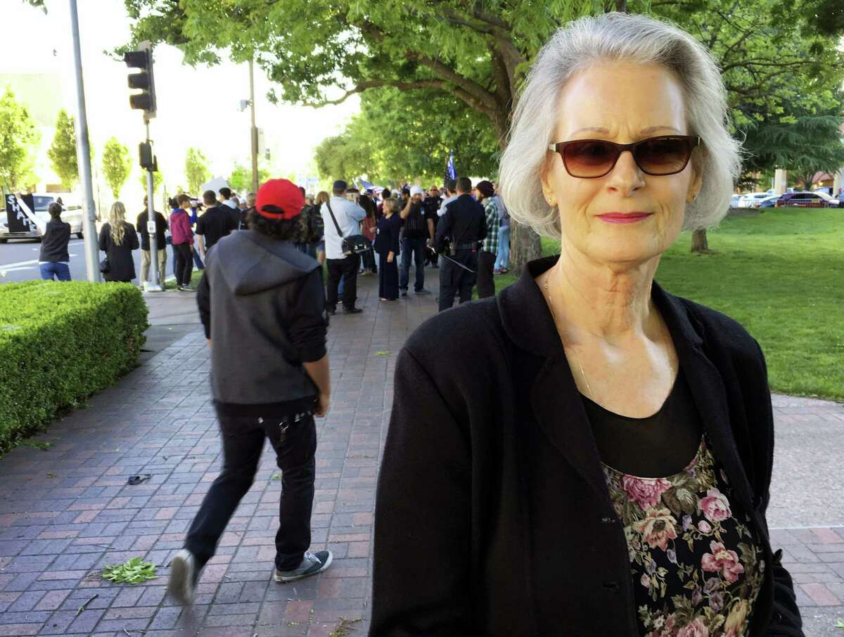 In this Friday, April 28, 2017, photo Kathleen Westenberg poses in front of demonstrators before walking into a speech by conservative commentator Ann Coulter in Modesto, Calif. Westenberg said she would like to see her congressman, Republican Jeff Denham, fight to fully repeal former President Barack Obama's health care law. The latest iteration of the GOP bill would let states escape a requirement under Obama's law that insurers charge healthy and seriously ill customers the same rates.