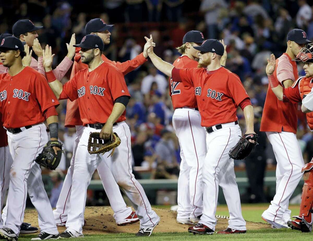 Boston Red Sox closer Craig Kimbrell, second from right, celebrates with teammates after they defeated the Chicago Cubs 5-4 in a baseball game at Fenway Park, Friday, in Boston.