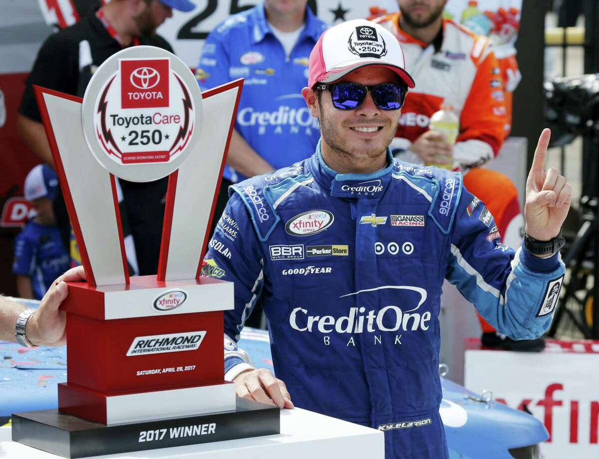Kyle Larson poses with the trophy in Victory Lane after winning the NASCAR Xfinity Series auto race at Richmond International Raceway in Richmond, Va., Saturday.