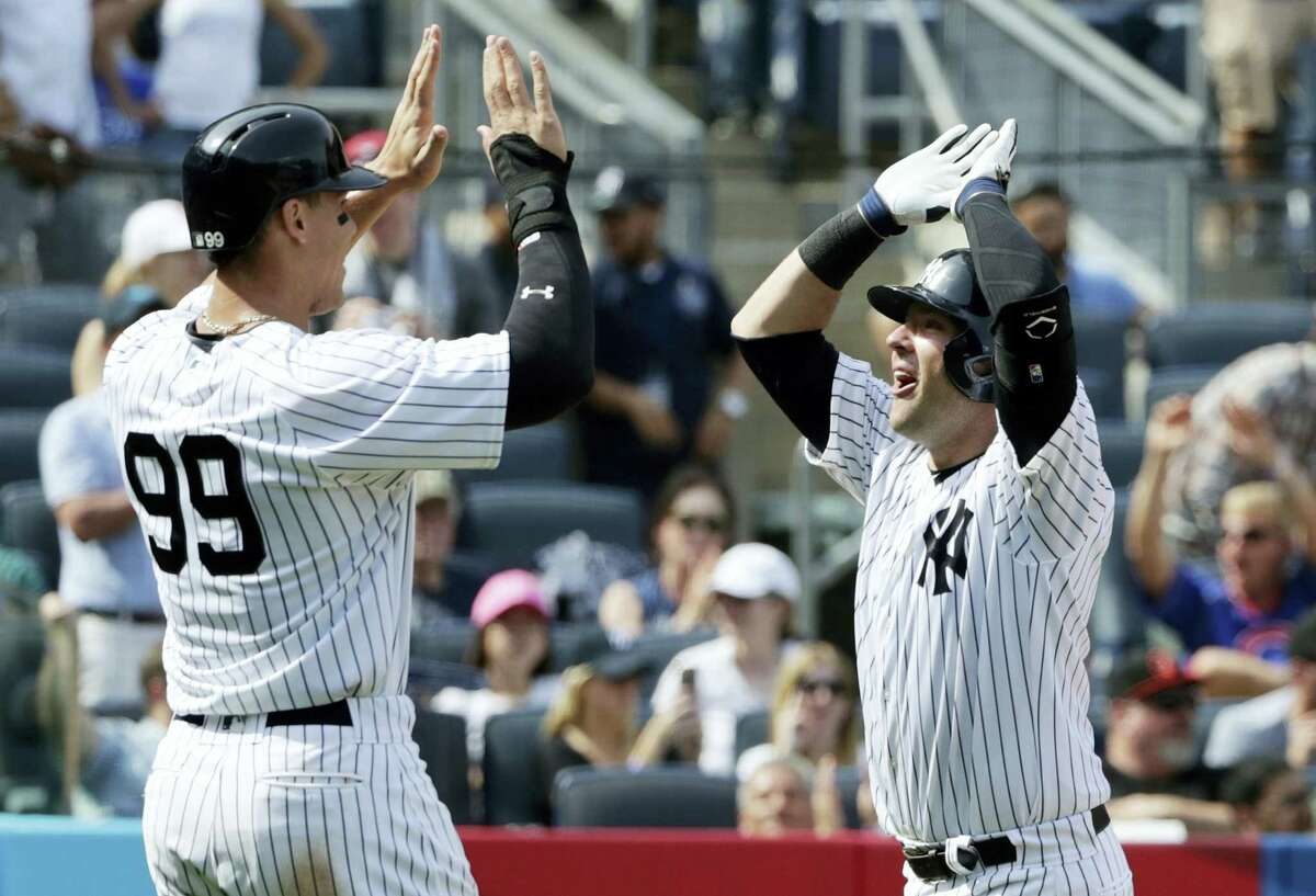 New York Yankees' Austin Romine, right, celebrates with teammate Aaron Judge, left, after Romine hit a 2-run home run during the sixth inning of a baseball game against the Baltimore Orioles, Saturday in New York.
