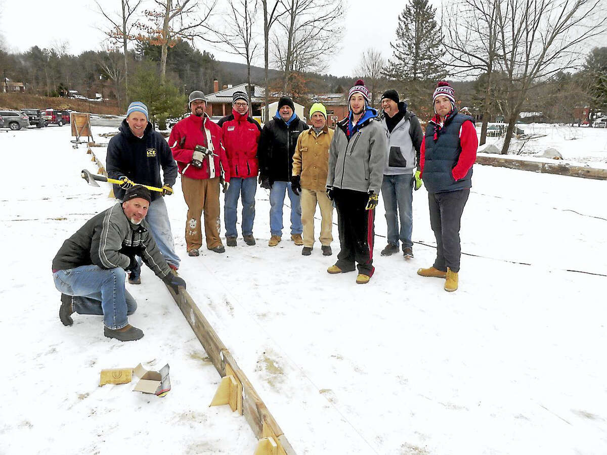 Contributed photosMembers of the Hartford Wolf Pack ice hockey team, wearing the red, white and blue hats, joined members of the Lions Club of Barkhamsted on Saturday to assemble the town ice skating rink at Barkhamsted Elementary School.