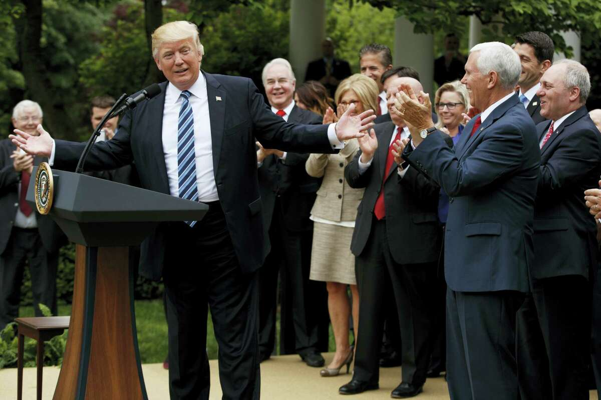 President Donald Trump, accompanied by GOP House members, speaks in the Rose Garden of the White House in Washington Thursday after the House pushed through a health care bill.