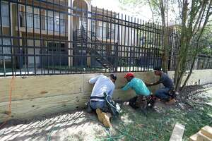 Workers place wood on the bottom of the  wrought iron fence surrounding the Biscayne Apartment Complex at 17050 Imperial Valley Drive, in the Greenspoint area, as they prepared to try to shore up the complex against the expected rain from Hurricane Harvey,  Thursday, Aug. 24, 2017, in Houston.  The apartment complex was flooded in the Tax Day floods in 2016.