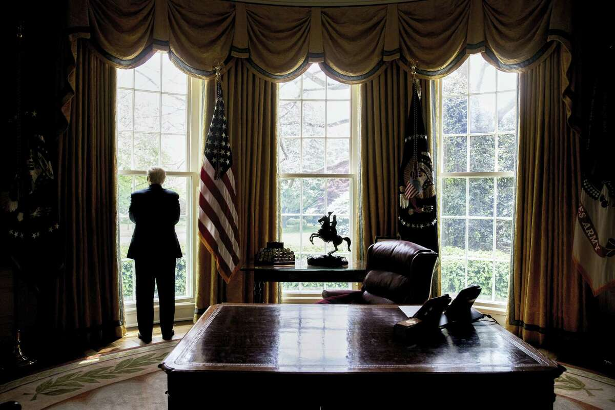 President Donald Trump looks out an Oval Office window at the White House in Washington following an interview with The Associated Press.