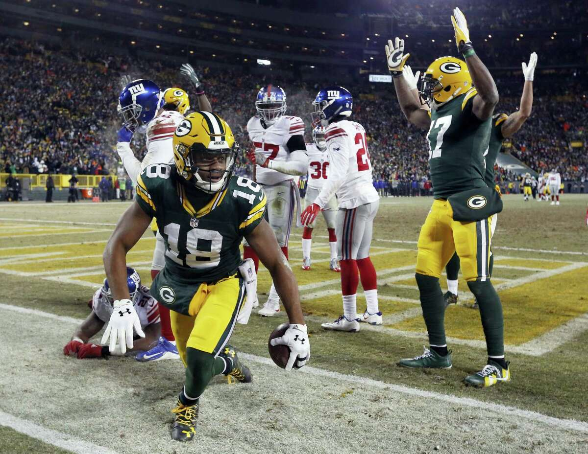 Packers wide receiver Randall Cobb (18) celebrates after catching a touchdown pass on a Hail Mary at the end of the first half Sunday.