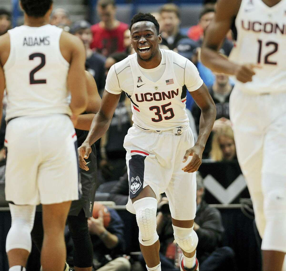 UConn's Amida Brimah smiles toward teammate Jalen Adams, left, in the first half of Sunday's game against Central Florida.
