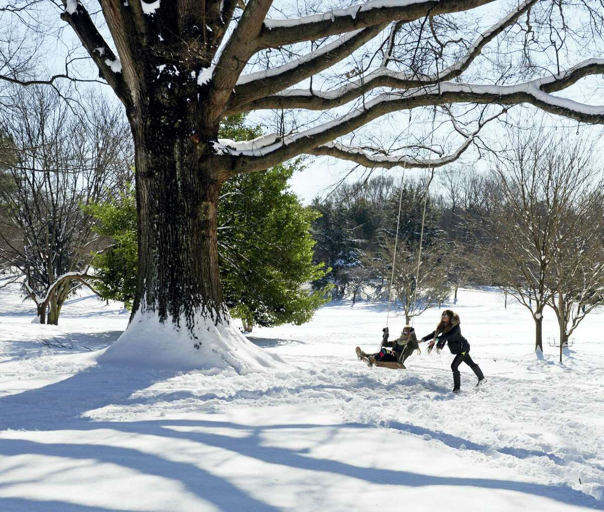 Vanessa Kirschner gives her friend, Victoria Koniuk, a push on a swing at Wake Forest's Davis Field Saturday, Jan. 7, 2017, in Winston-Salem, N.C. The two freshmen were back on campus for sorority rush but that was delayed because of the snow. Classes are scheduled to begin again on Tuesday. (Walt Unks/The Winston-Salem Journal via AP)