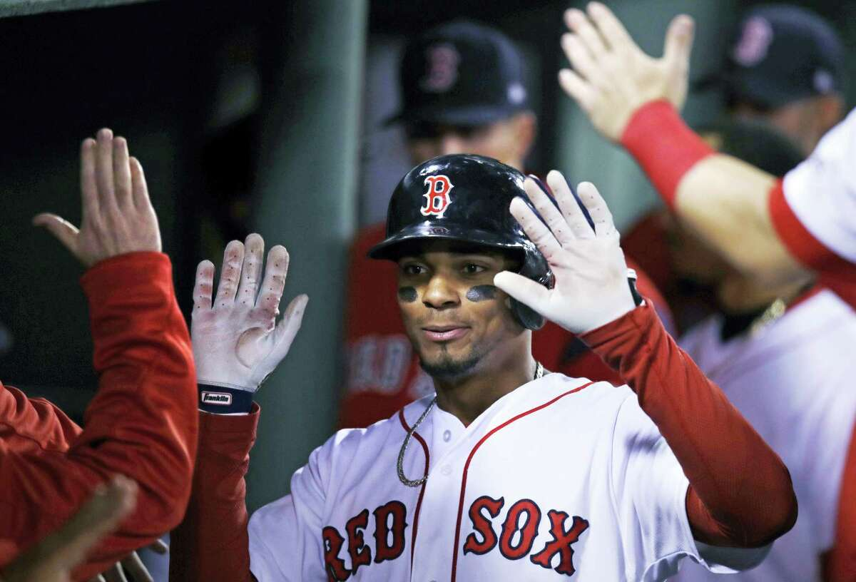 Boston's Xander Bogaerts is congratulated by teammates after scoring on a double by Chris Young during the fourth inning against the Baltimore Orioles at Fenway Park in Boston.
