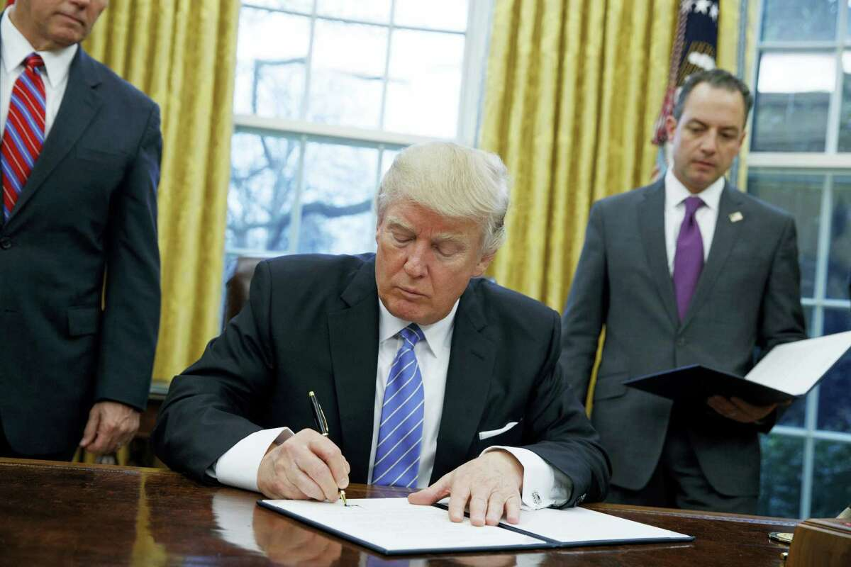 President Donald Trump signs an executive order to withdraw the U.S. from the 12-nation Trans-Pacific Partnership trade pact agreed to under the Obama administration in the Oval Office of the White House in Washington.