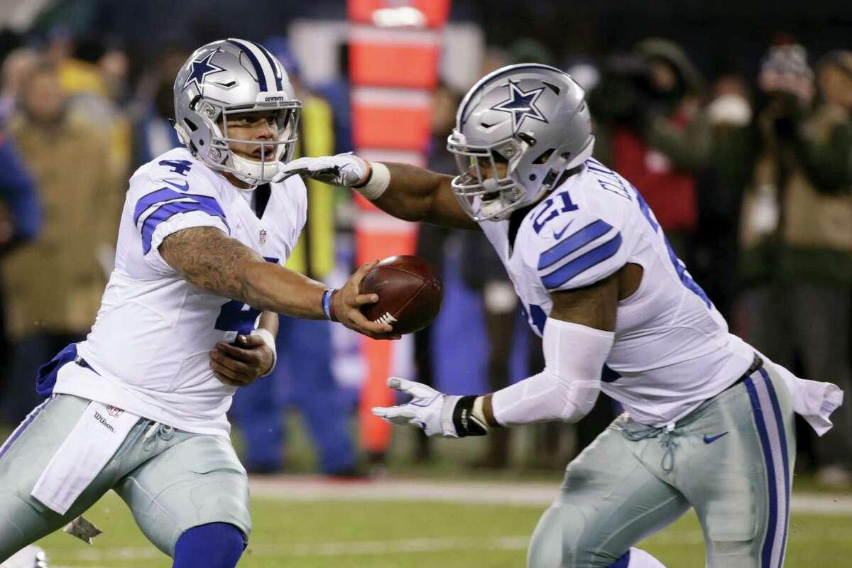 Dallas Cowboys quarterback Dak Prescott hands the ball to Ezekiel Elliott during a game this season.