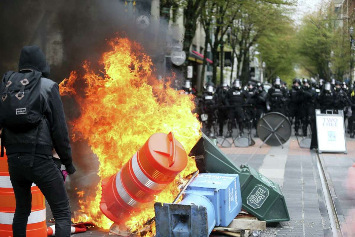 Police try to disperse people participating in a May Day rally in downtown Portland, Ore., Monday. Police in Portland said the permit obtained for the May Day rally and march there was canceled as some marchers began throwing projectiles at officers.