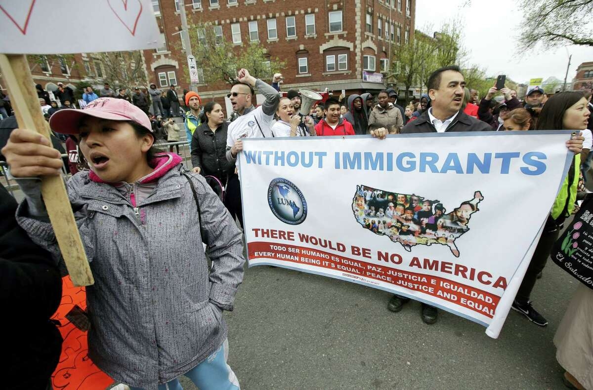 Demonstrators display placards and chant slogans during a May Day rally, Monday in Chelsea, Mass. Thousands of people chanted, picketed and marched on cities across America on Monday as May Day demonstrations raged against President Donald Trump's immigration policies.