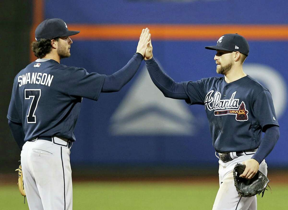 Atlanta Braves second baseman Jace Peterson, right, and shortstop Dansby Swanson celebrate after the Braves defeated the New York Mets 8-2 in a baseball game, Wednesday in New York.