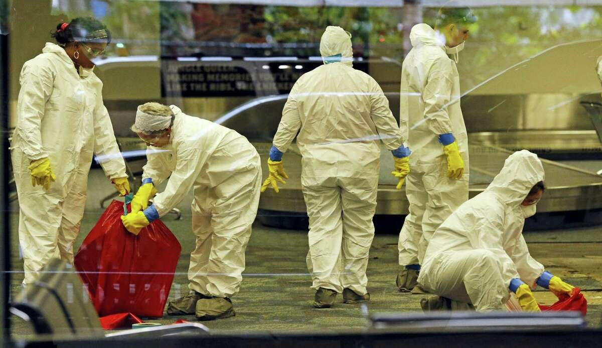 A hazmat crew cleans up baggage claim Terminal Two on Saturday, Jan. 7, 2017 at Fort Lauderdale-Hollywood International Airport Terminal the day after multiple people were shot on Friday.