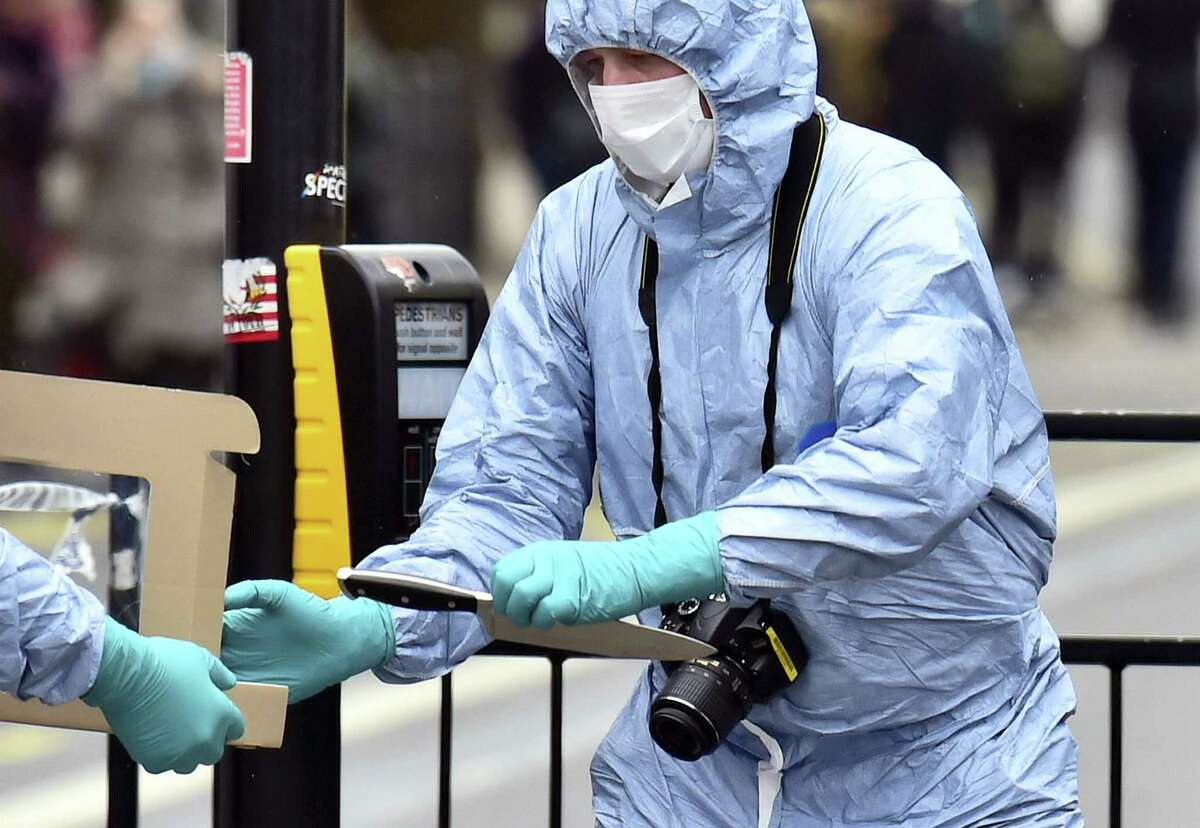 A police forensic officer holds a knife at the scene after a man was arrested following an incident at Whitehall in London, Thursday April 27, 2017. London police arrested a man for possession of weapons Thursday near Britain's Houses of Parliament.