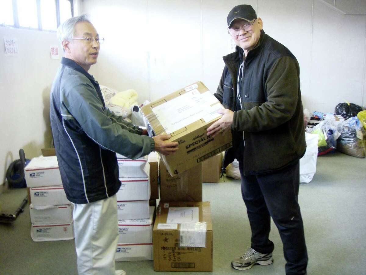 Joseph Roginski, right, holds a package in a storeroom of the Misawa City Hall in Japan, where donations of clothing and supplies were being kept for earthquake relief efforts. He says that while the cost of living is higher in Japan, access to health care is not.