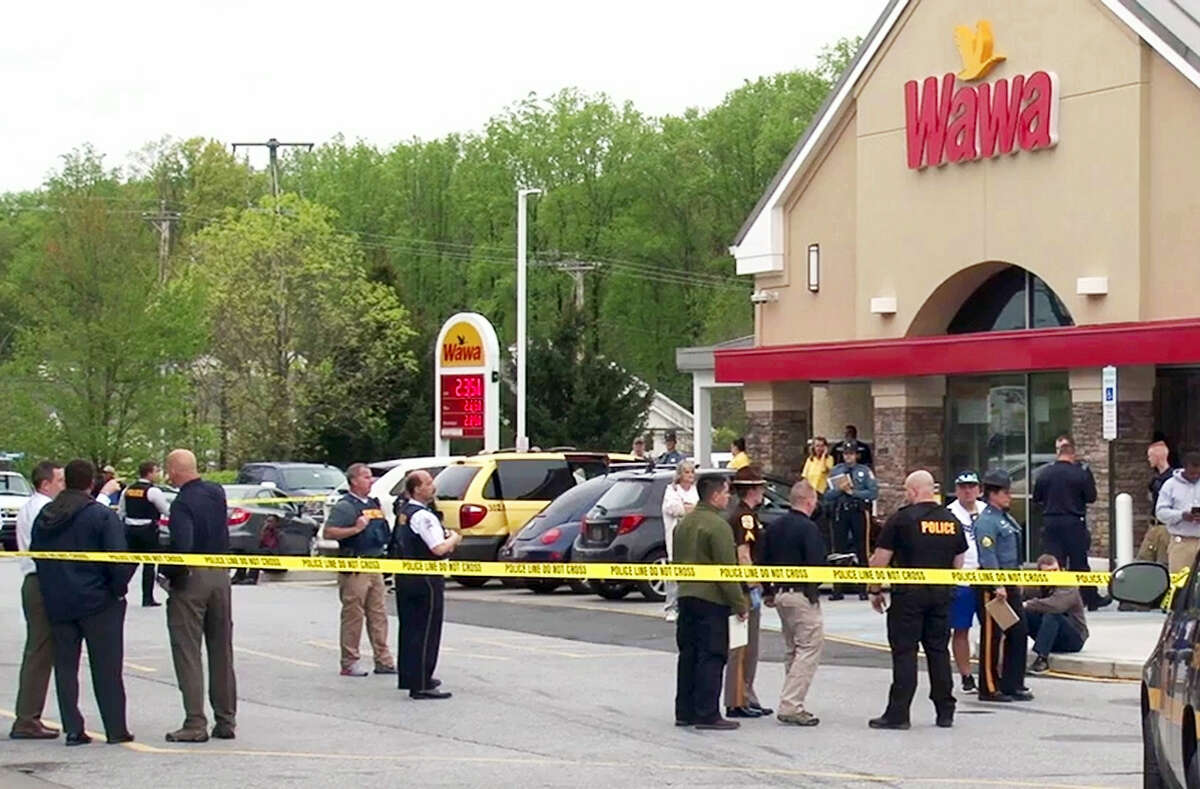 Authorities investigate the scene of a shooting on Wednesday, April 26, 201 in Bear, Del. Delaware State Police say a trooper has been taken to a hospital after being shot at the convenience store. The trooper, who was on duty at the time, was taken to Christiana Hospital but died of his injuries.