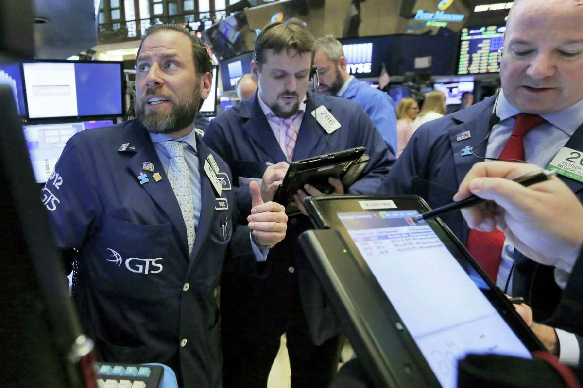 Specialist Michael Pistillo, left, works with traders at his post on the floor of the New York Stock Exchange Tuesday.