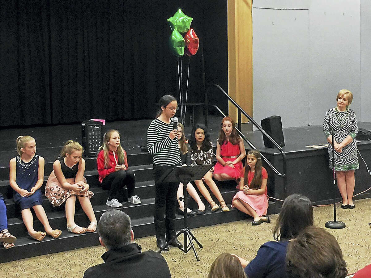 """New Hartford students and community members recited poems with a culinary theme Monday evening, as part of the launch for """"Poetry for the Pantry: Feed A Body, Feed Your Soul."""" Proceeds from the book's sales will benefit the Connecticut Food Bank. The event's founder, Sheila Hawley stands to the right of the stage."""